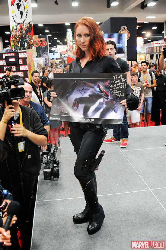 SDCC 2012: A fan poses with her autographed poster during the Don Cheadle and Shane Black signing on the Marvel Stage