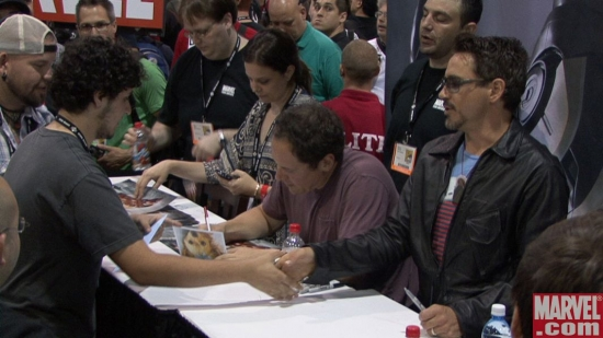 Jon Favreau and Robert Downey Jr. sign some autographs